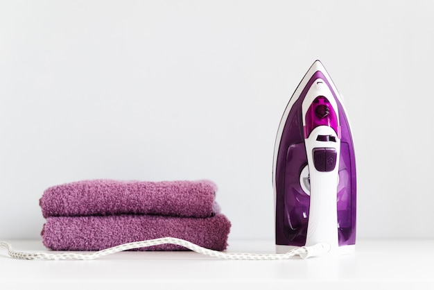Front view purple iron with stacked towels Free Photo