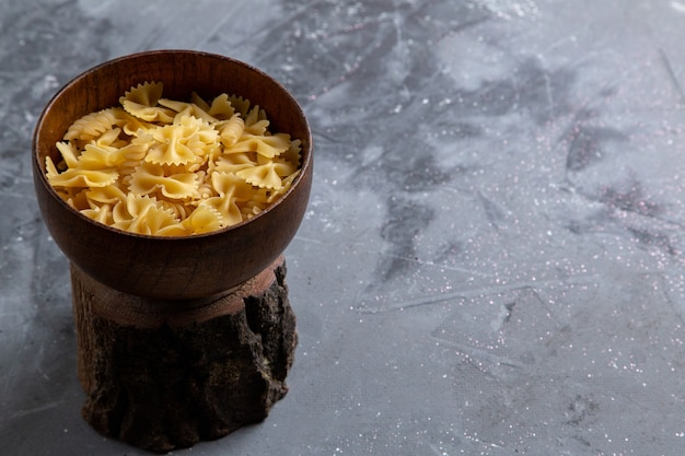 A front view raw italian pasta little formed inside brown plate on the grey table pasta italian food meal Free Photo