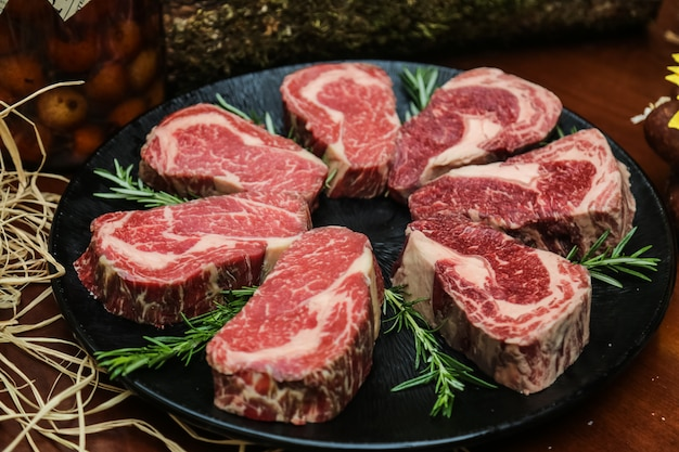 Front view raw marbled meat for steak with rosemary on a stand Free Photo