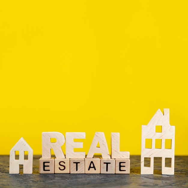 Front view real estate lettering on yellow background Premium Photo