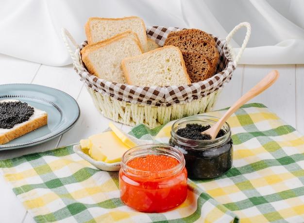 Vista frontale caviale rosso e nero in barattoli di vetro con burro e pane in un cestino Foto Gratuite