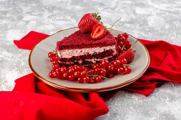 Vista frontale fetta di torta rossa fetta di torta di frutta all'interno della piastra con mirtilli rossi freschi e fragole alogn con tessuto rosso su grigio Foto Gratuite