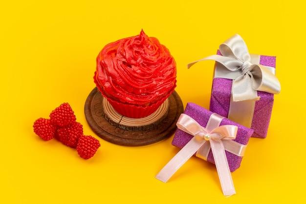 Una torta rossa vista frontale con lamponi freschi e contenitori di regalo viola sullo scrittorio giallo Foto Gratuite