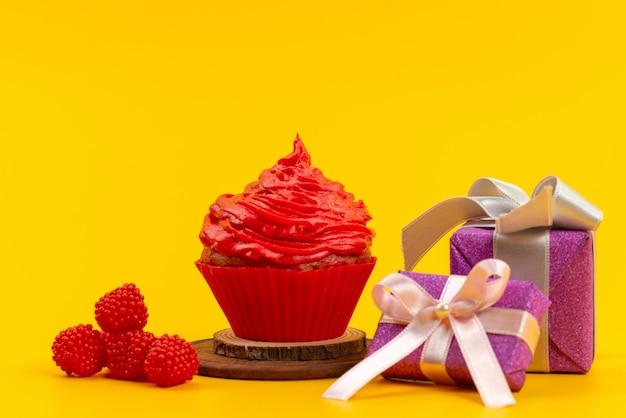 Una torta rossa di vista frontale con lamponi rossi freschi e contenitori di regalo viola sullo scrittorio giallo Foto Gratuite