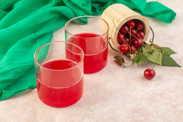 Una spremuta della ciliegia rossa di vista frontale con le ciliege fresche sul cocktail rosa della bevanda di colore della frutta dello scrittorio Foto Gratuite