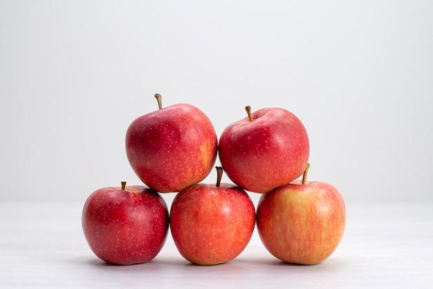 Вид спереди красные свежие яблоки, выложенные на белом столе, фрукты, свежие спелые спелые деревья Бесплатные Фотографии