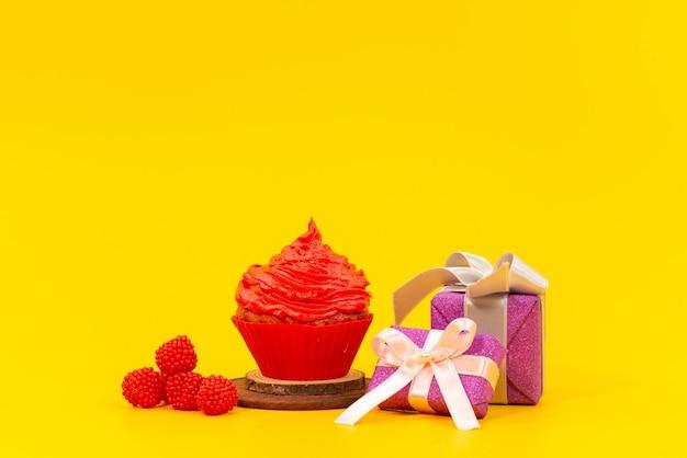 Una torta di frutta rossa vista frontale con lamponi rossi freschi e contenitori di regalo viola sullo scrittorio giallo Foto Gratuite