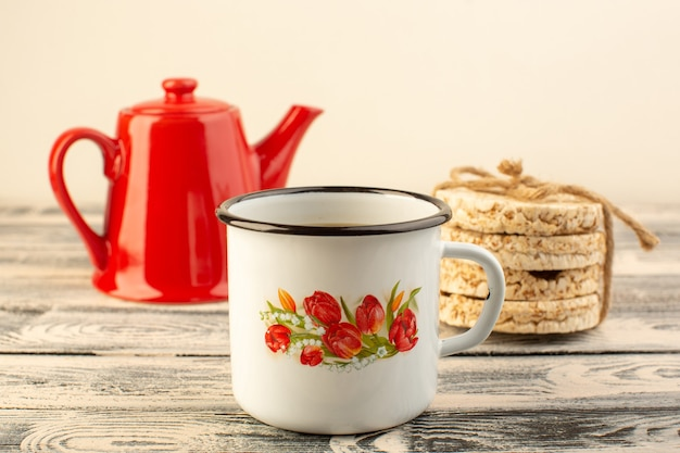 A front view red kettle with cup of coffee and crackers on the grey rustic table drink coffee color Free Photo