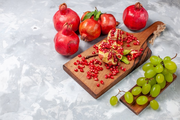 Front view red pomegranate fresh and juicy fruits with grapes on white desk Free Photo