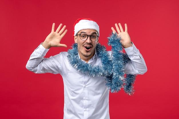 赤い壁のクリスマスの人間の休日に新年を祝う正面図通常の男性 無料写真