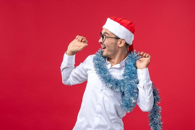 赤い壁の人間のクリスマス休暇で新年を祝う正面図通常の男性 無料写真