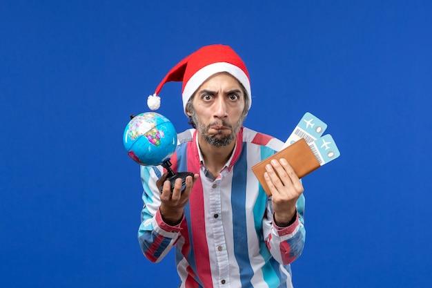 地球儀と青い机の感情の休日の新年のチケットを持つ正面図通常の男性 無料写真