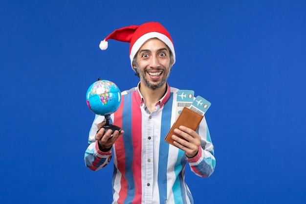 파란색 벽 휴일 새해 색상에 티켓과 글로브가있는 전면보기 일반 남성 무료 사진
