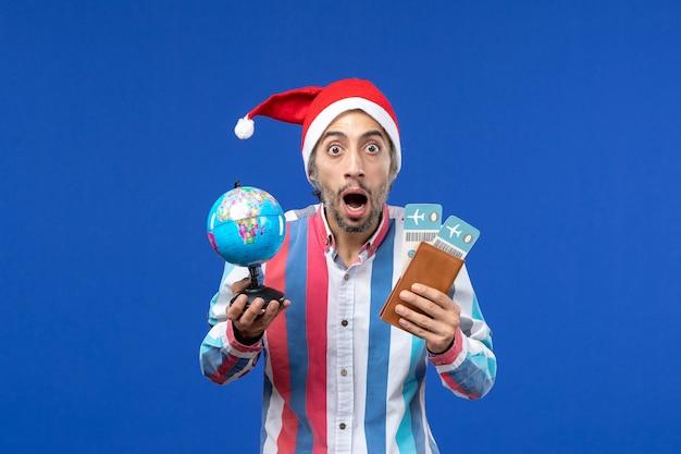파란색 책상 휴일 새해 색상에 티켓과 글로브가있는 전면보기 일반 남성 무료 사진