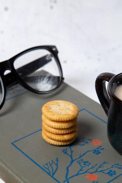 Вид спереди круглое печенье с солнцезащитными очками и чашка молока на хрустящей закуске с крекером из белого печенья Бесплатные Фотографии