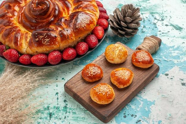 Vista frontale rotonda deliziosa torta con fragole rosse fresche e torte sulla superficie blu chiaro torta di zucchero torta biscotto biscotto dolce Foto Gratuite