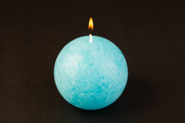 A front view round shaped candle lighting blue colored designed on the dark background bright fire decoration Free Photo
