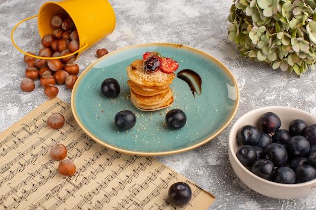 Vista frontale patatine salate progettate con fragole all'interno del piatto insieme a prugnoli sul tavolo bianco, frutti di bosco snack patatine fritte Foto Gratuite