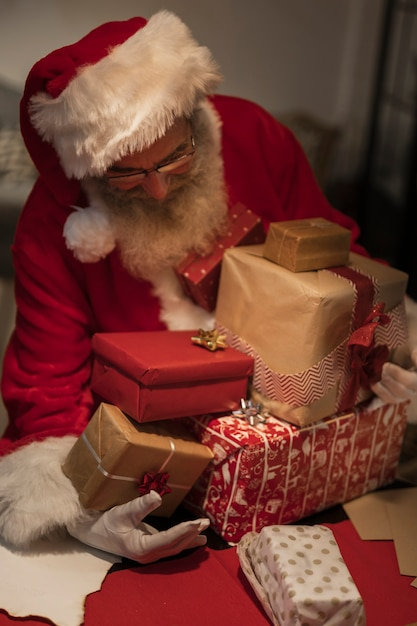 Front view santa claus holding gift boxes Free Photo