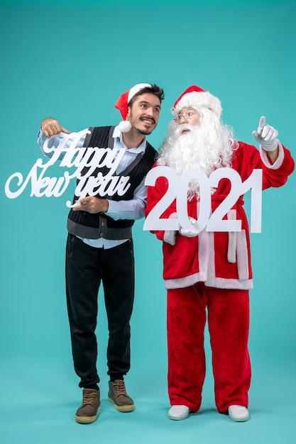 Vista frontale di babbo natale con maschio che tiene felice anno nuovo e 2021 banner sulla parete blu Foto Gratuite