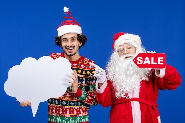 白い看板と販売の書き込みを保持している若い男性と正面のサンタクロース 無料写真