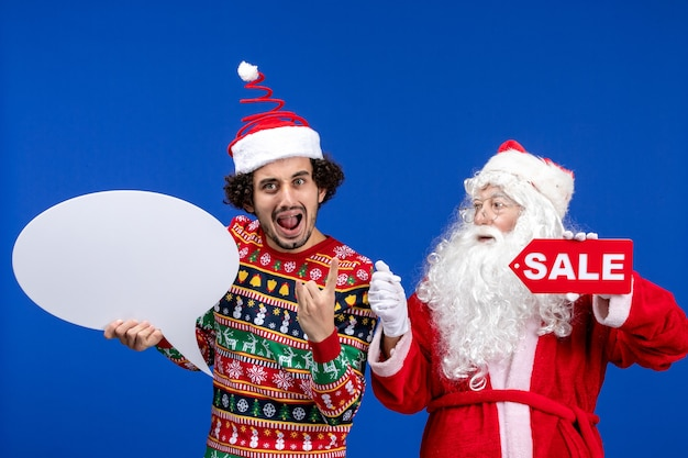 Front view santa claus with young male holding white sign and sale writing Free Photo