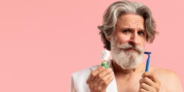 Vista frontale dell'uomo barbuto senior con la lama e la schiuma di rasatura Foto Gratuite
