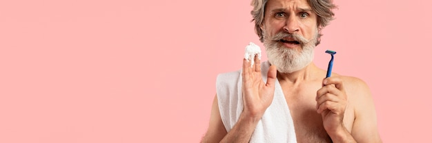 Vista frontale dell'uomo barbuto senior con la lama di rasatura Foto Gratuite
