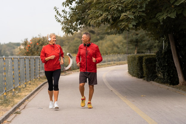 Front view of senior couple jogging together outside in the park Free Photo