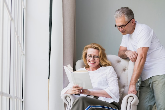 Front view senior couple reading a book Free Photo