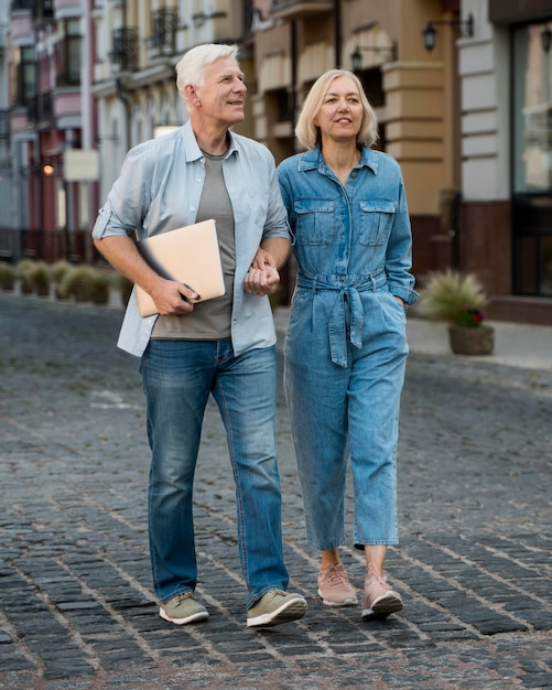 Front view of senior couple with tablet taking a walk in the city Free Photo