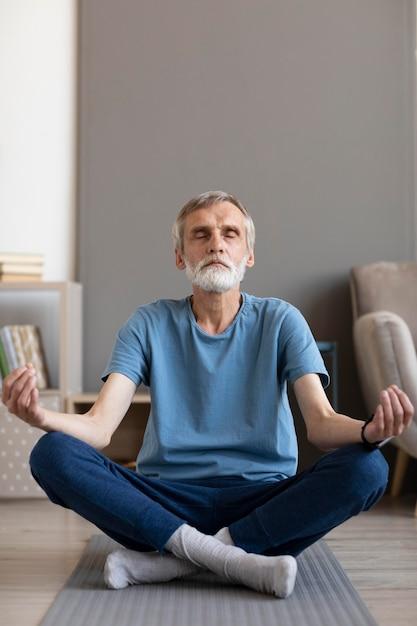 Front view senior male meditating Free Photo