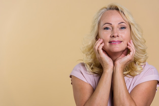 Front view senior woman looking at the camera with beige background Free Photo