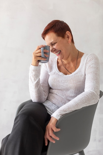 Front view senior woman with mug laughing Free Photo