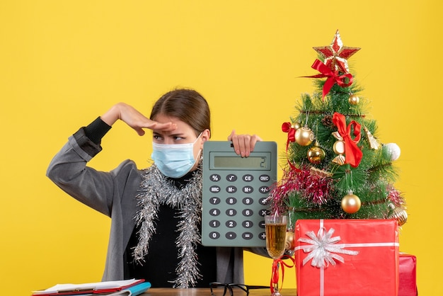 Front view serious girl with medical mask sitting at the table holding calculator putting hand Free Photo