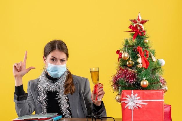 Ragazza seria di vista frontale con mascherina medica che si siede al tavolo tostando albero di natale e regali cocktail Foto Gratuite
