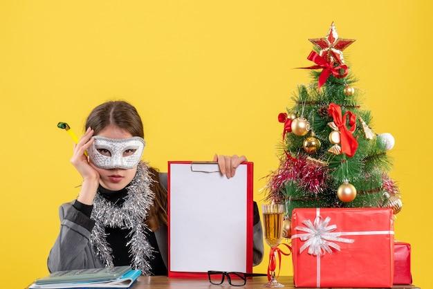 ノイズメーカーのクリスマスツリーとギフトカクテルを保持しているテーブルに座っているマスクを持つ真面目な少女の正面図 無料写真