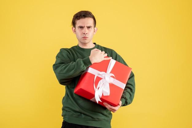 Вид спереди серьезный молодой человек с зеленым свитером, стоящий на желтом Бесплатные Фотографии