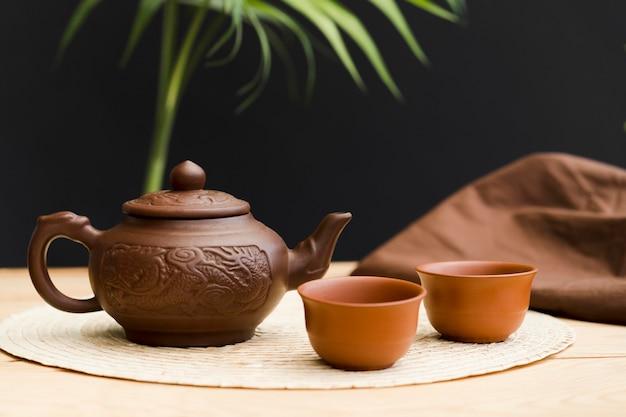 Вид спереди с чайником и чайной чашкой Premium Фотографии