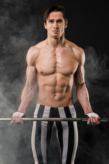Front view of shirtless athletic man holding weight set Free Photo