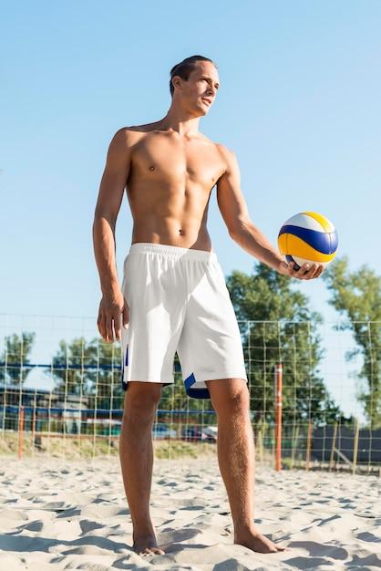 Vista frontale del giocatore di pallavolo maschio senza camicia sulla spiaggia con la palla Foto Gratuite