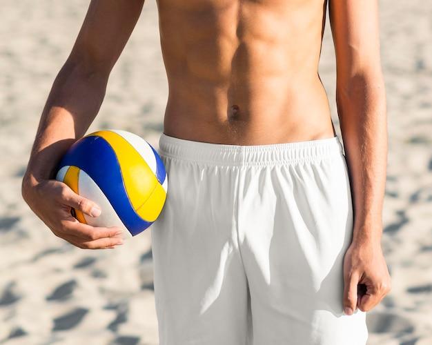 Vista frontale del torso maschio senza camicia del giocatore di pallavolo che tiene la palla sulla spiaggia Foto Gratuite