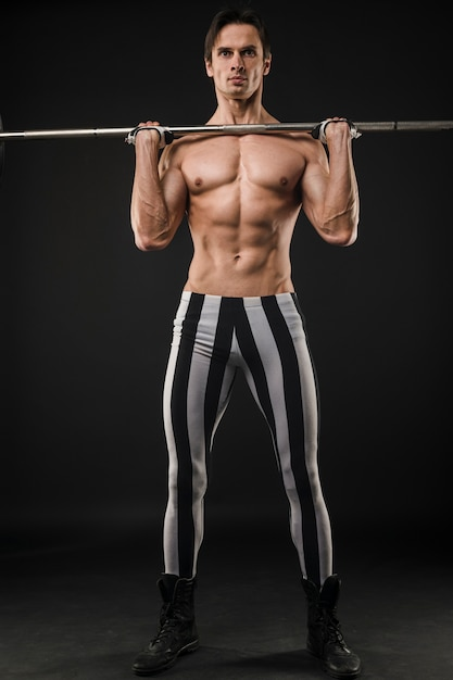 Front view of shirtless muscled man lifting weights Free Photo