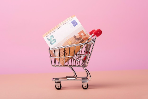 Front view of shopping cart with banknotes Free Photo