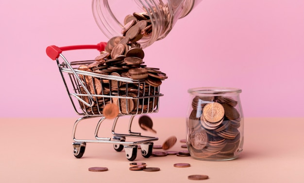 Front view of shopping cart with lots of coins and jar Free Photo