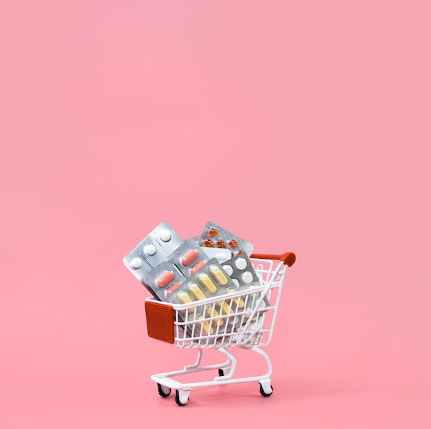 Front view of shopping cart with pill foils and copy space Free Photo