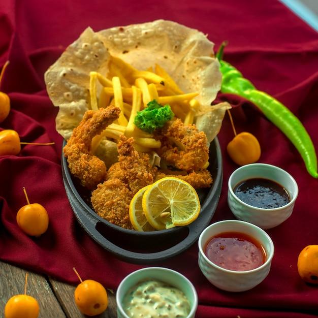 Вид спереди креветки в кляре с картофелем фри жареный лаваш и соусы Бесплатные Фотографии