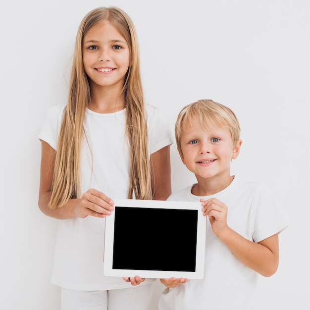 Front view siblings holding a tablet mock-up Free Photo