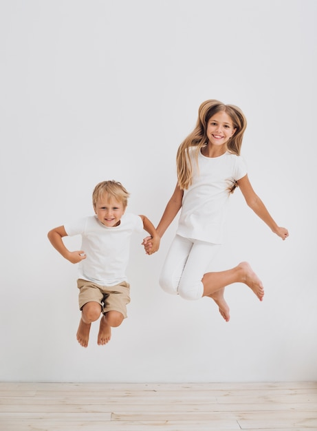 Front view siblings jumping together Free Photo