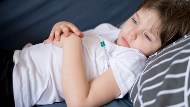 Front view sick child sitting in bed Free Photo